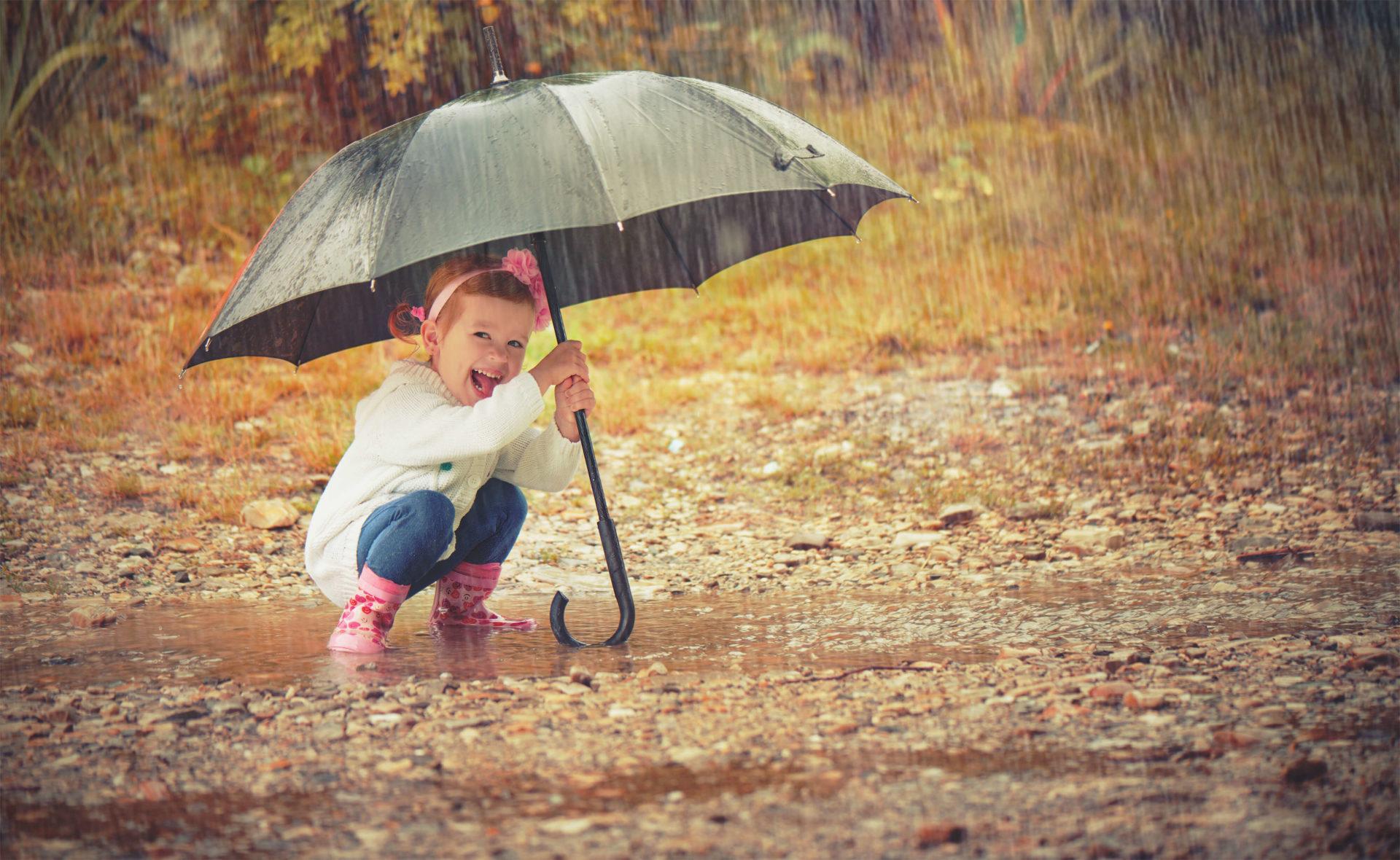 Little girl holding umbrella in the rain